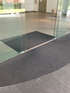 The picture shows a glazed frameless door with an entry mat on one side.  The entry mat can be a tactile indication as to where the entry doorway is located